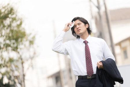 汗を拭いている男性